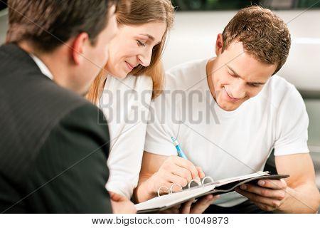 paar unterzeichnen Kaufvertrag bei Autohändler