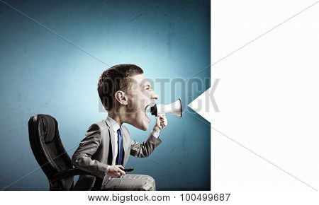 Funny young man with big head screaming emotionally in megaphone