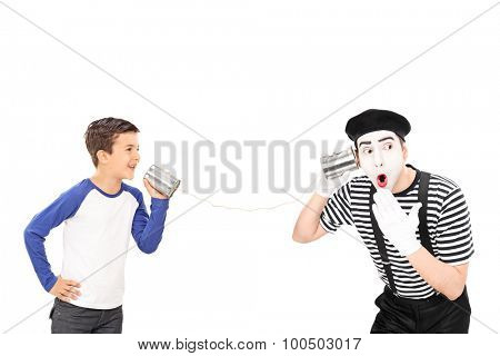 Studio shot of a little kid talking to a young male comedian through a tin can phone isolated on white background