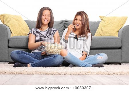 Two teenage girls looking at the camera and laughing seated on the floor in front of a gray sofa isolated on white background