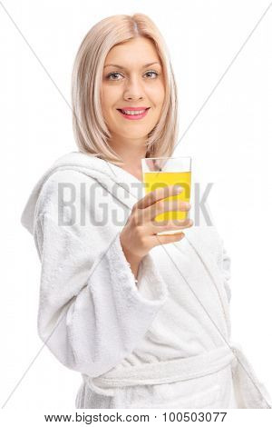 Vertical shot of a cheerful young girl in a white bathrobe holding an orange juice and looking at the camera isolated on white background