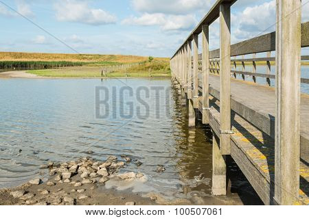 Side Of A Wooden Footbridge Over A Creek