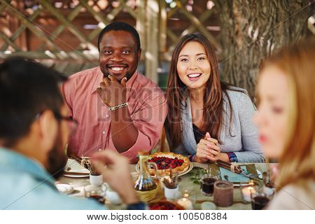 Happy young couple looking at camera by Thanksgiving table