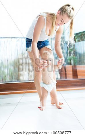 Baby taking first steps with mothers help