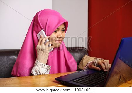 Young Muslim Women Speak To The Phone While Using Laptop