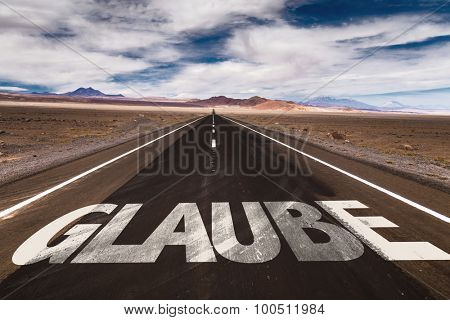 Believe (in German) written on desert road