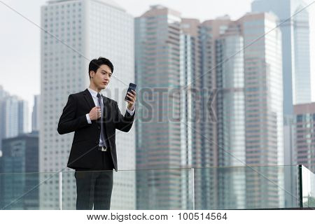 Businessman with mobile phone at oudoor