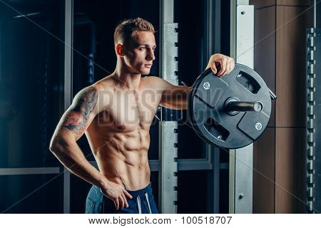 Closeup portrait of a muscular man workout with barbell at gym. Brutal bodybuilder athletic six pack
