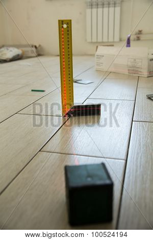 Laser Level With A Square On The Floor Tiles.