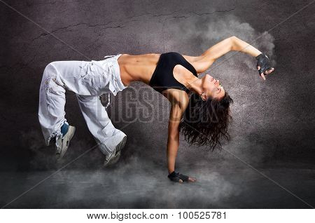 Young beautiful athletic woman jumping dancing modern style dance hip-hop on studio on wall backgrou
