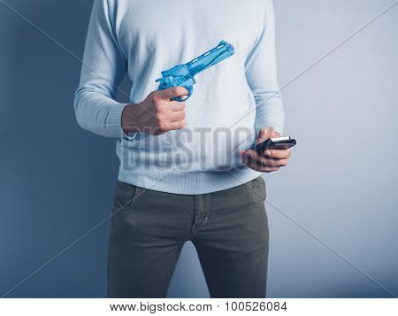 Man With Water Pistol And Smart Phone