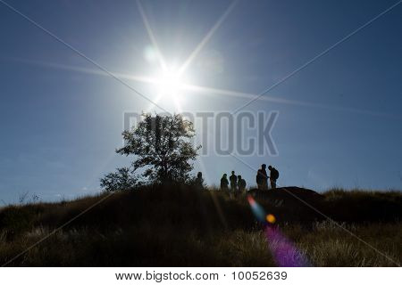 Silhouette Of Young People On A Hill
