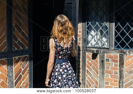 Young Woman Opening Door And Entering Old Building