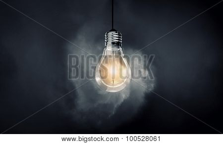 Glowing light bulb on dark background hanging from above