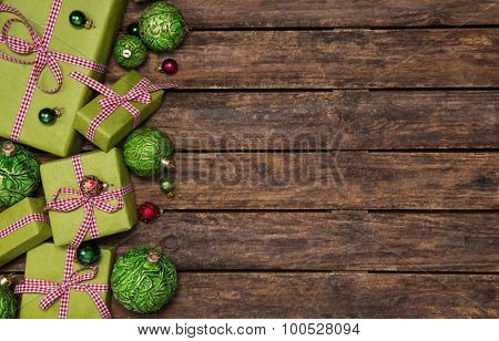 Red and apple green christmas presents with a checked ribbon on old dark brown wooden background.