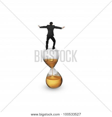 Businessman Balancing On Hourglass