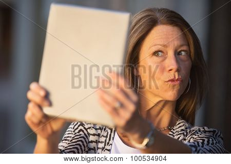 Woman Puckering Lips At Tablet