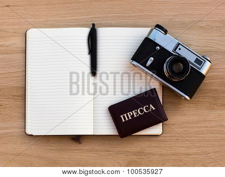 Russian Press card, open a Notepad, pen and a film camera, a top view of the tree oak texture.