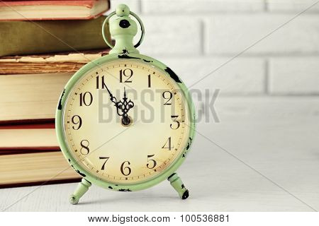 Clock and vintage books, on light wall background