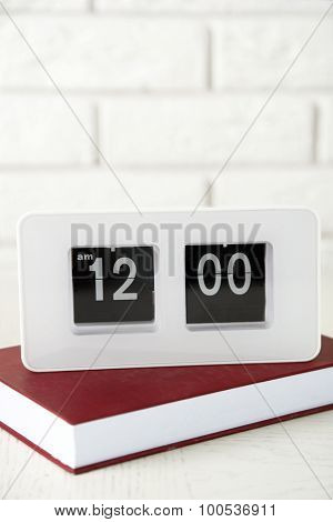Modern Clock and book, on light wall background
