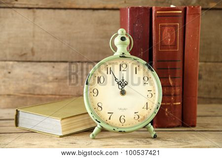Clock and vintage books, on rustic wooden background