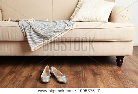 Female dress on sofa near shoes on floor in room