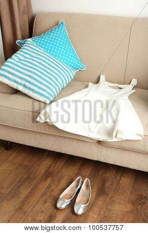 White female dress on sofa and ballet shoes on floor in room
