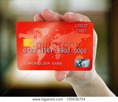 Hand holding credit cards on abstract background