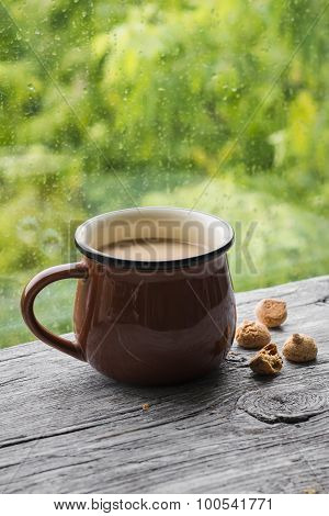 Tea With Milk And Biscuits On A Light Wooden Surface Against Window With Rainy Day View