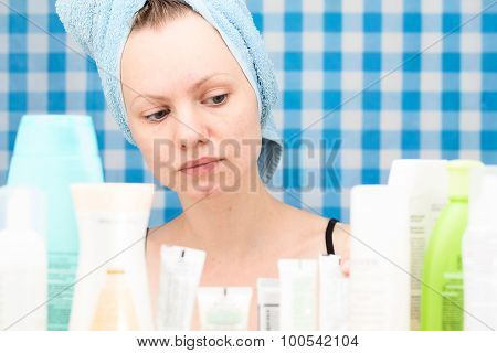 Girl Is Looking At Cosmetic Products In Bathroom