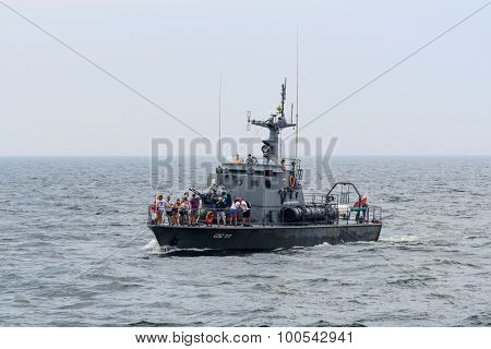 KOLOBRZEG - AUGUST 12: Tourists enjoying the sunny weather and a cruise military ship on the sea on 12 August 2015 in Kolobrzeg, Poland. It is an old military frigate converted into a tourist ship.