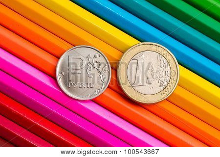 coins on colored pencils