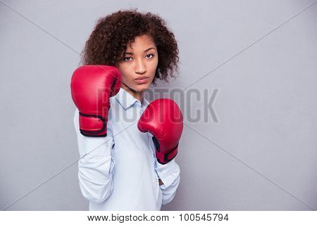 Portrait of a beautiful afro american woman in boxing gloves on gray background