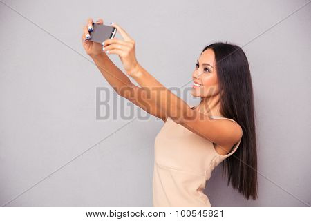 Portrait of a happy cute woman making selfie photo on smartphone over gray background