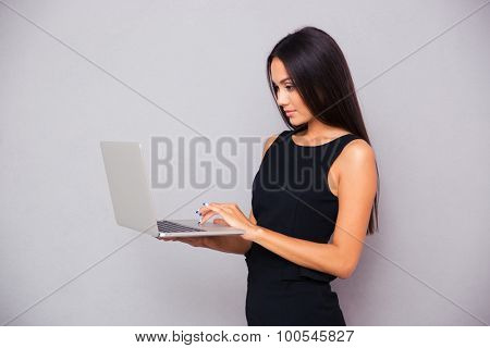 Portrait of a beautiful businesswoman using laptop on gray background