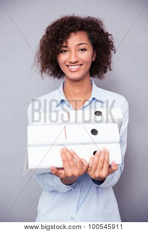 Portrait of a cheerful afro american businesswoman holding folders on gray background and looking at camera