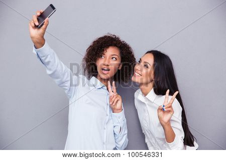 Portrait of a happy two girls making selfie photo on smartphone while showing two fingers sign on gray background