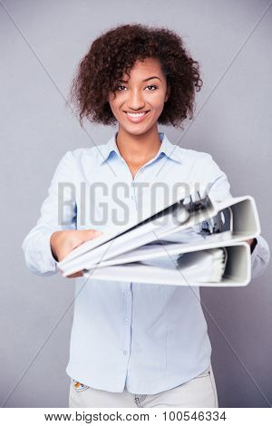 Portrait of a happy afro american woman giving folders at camera on gray background