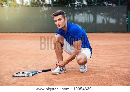Handsome male tennis player tying shoelaces outdoors