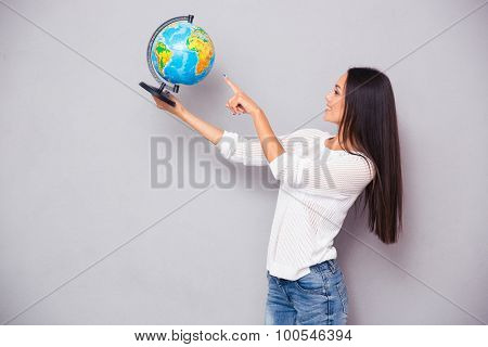 Portrait of a happy beautiful woman pointing finger at globe on gray background