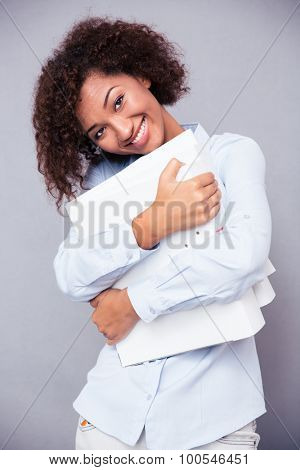 Portrait of a cute smiling afro american woman standing with folders on gray background and looking at camera
