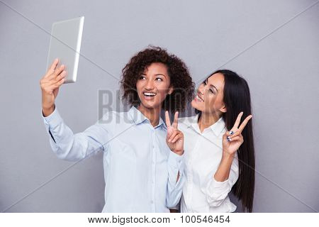 Portrait of a happy two girls making selfie photo on tablet computer while showing two fingers sign on gray background