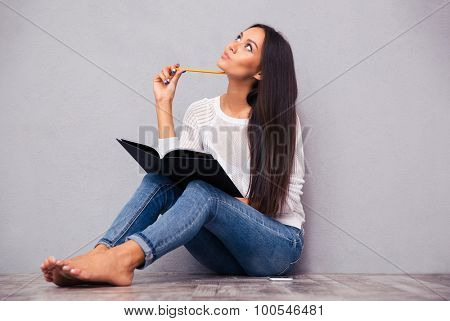Portrait of a pensive girl sitting on the floor with notepad and pencil on gray background