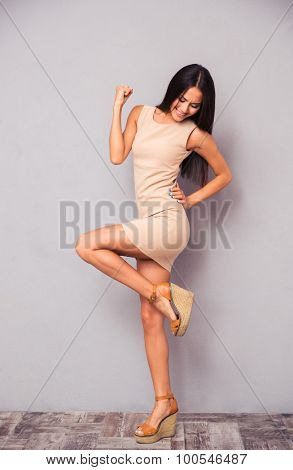 Full length portrait of a charming woman celebrating her success on gray background