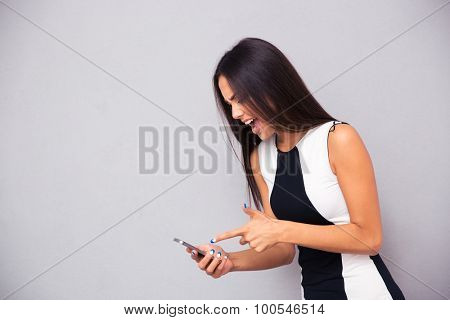 Portrait of elegant woman screaming on smartphone over gray background