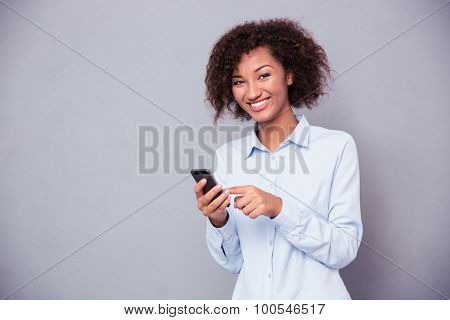Portrait of a smiling afro american woman using smartphone and looking at camera over gray background