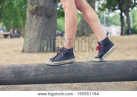 Woman Walking On Wooden Beam Outside In Park