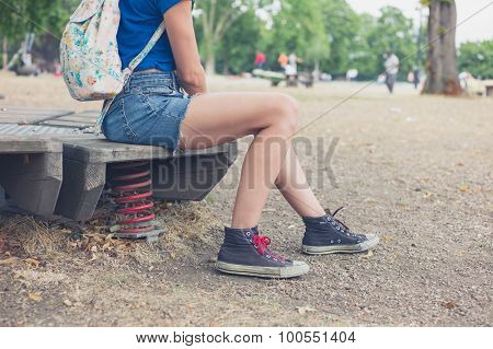 Young Woman Sitting On Playground Equipment Outside