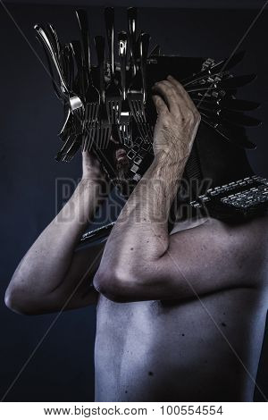 naked man with a crown of spoons and knives in the head, king of the kitchen