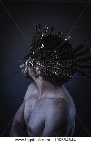 Angry, naked man with a crown of forks and knives in the head, concept designer kitchen